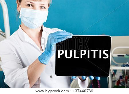 technology, internet and networking in medicine concept - femail dentist holding a tablet pc with pulpitis sign. at the dental equipment background.