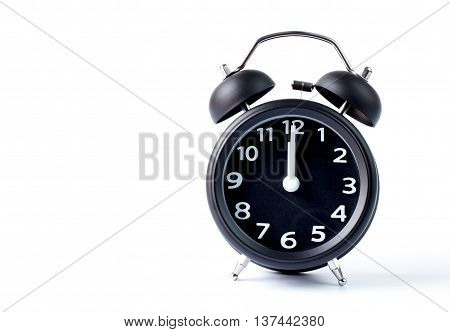 Black double bell alarm clock showing midnight on white background