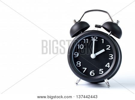 Black double bell alarm clock showing two o'clock on white background