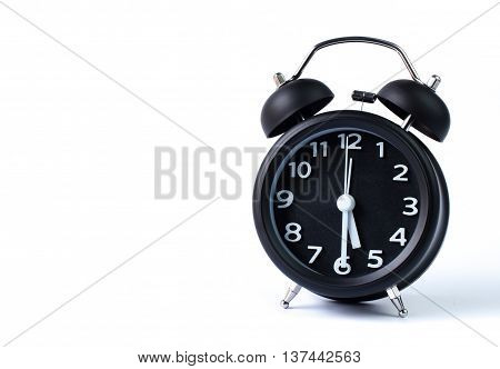 Black double bell alarm clock showing half past five on white background