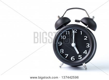 Black double bell alarm clock showing five o'clock on white background