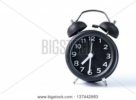 Black double bell alarm clock showing half past seven on white background