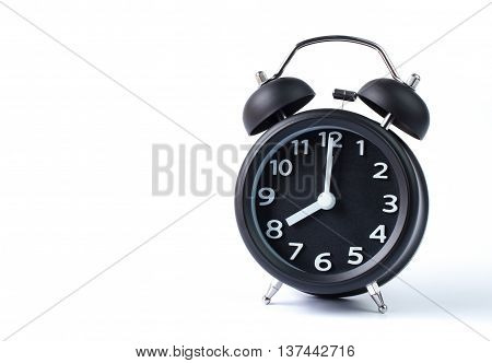 Black double bell alarm clock showing eight o'clock on white background