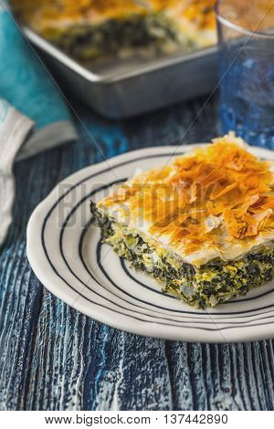 Greek pie spanakopita in the white plate on the blue wooden table