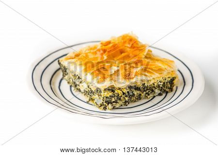 Piece of Greek pie spanakopita on the ceramic plate on the white background