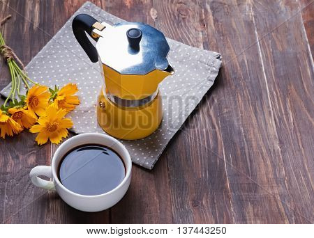 Coffee maker yellow flowers and cup with coffee on wooden table.