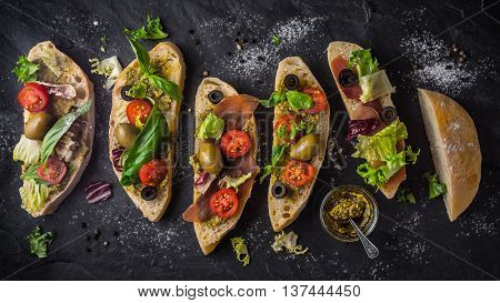 Slices of ciabatta with olives tomatoes and basil on the black stone table wide screen