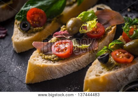 Slices of ciabatta with olives tomatoes and basil on the black stone table horizontal