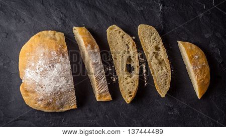 Sliced ciabatta on the dark stone table top view
