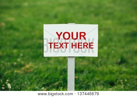 your text here sign against green grass background