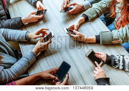 circle of people's hands using touchscreen on smart phones top view