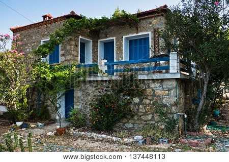 Greek house traditionaly made of stone with blue and white colored windows in Sithonia, Greece