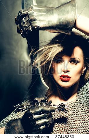 young pretty female warrior in silver chain armour and iron gloves with long hair an d sexy red lips holding ancient sword closeup