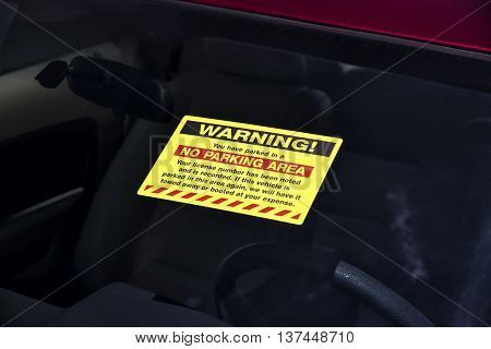 Yellow Parking Violation Sticker On Windshield Horizontal
