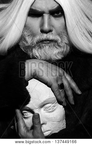old druid bearded man with long beard on serious face and hair in fur coat holding sculpture head in hands with ring black and white