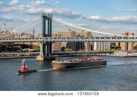 Manhattan Bridge with the city skyline behind. A cargo ship passes underneath it.