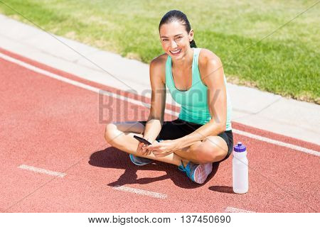 Portrait of happy female athlete using mobile phone on running track