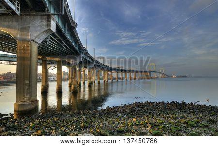 Throgs Neck bridge seen from below. Sunset light shine on the bridge's pillars.