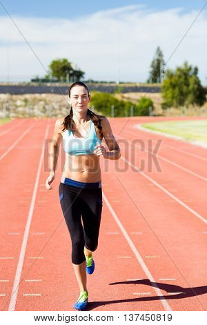 Happy female athlete running on the running track on a sunny day
