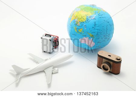 Airplane, suitcase, guidebook, and globe. overseas travel concept.