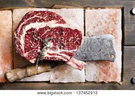 Bone In Rib Eye row Steak on pieces of salt on a wooden board. Stock image