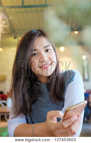 Charming Asian Woman With Beautiful Smile Reading Off Touch Phone