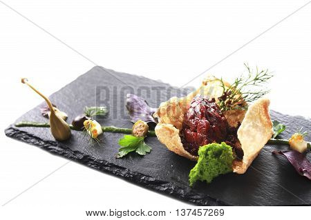 Molecular modern cuisine. Chips Pigskin with tartare or carpaccio of beef. Stock image. Isolated on white.