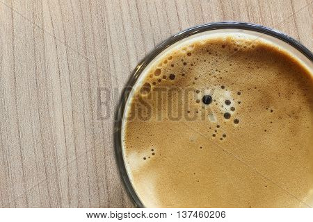 Coffee cup with black coffee on wooden table (top view)