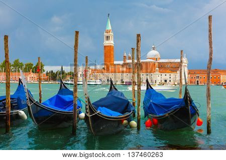 Gondolas moored by Saint Mark square with San Giorgio di Maggiore church in the background in Venice lagoon after the storm, Italia