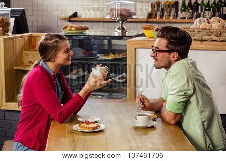Couple sitting at table and talking in cafeteria