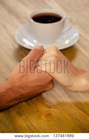 Close-up of couple holding hands in cafeteria