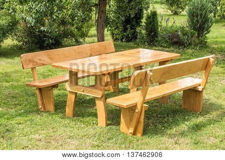 Wooden set of table benches with backrests on green grass lawn. Vacation place in garden. Summer leisure time.