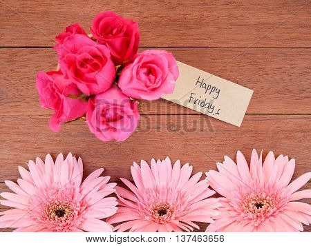 Rose pink Gerbera flower pink rose flower and handwriting Happy Friday on brown label paper with dark wood background