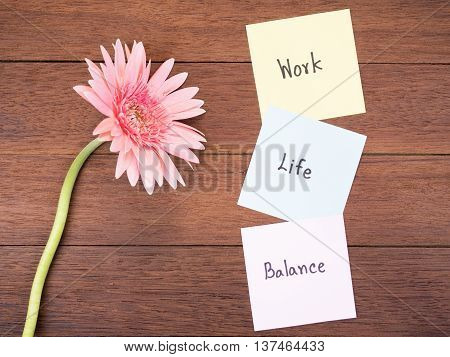 Handwriting word Work Life Balance on notepaper and pink Gerbera daisy flower with wood background
