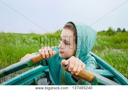 boy rowing a wooden boat. child controls rowing boat near the shore. Closeup