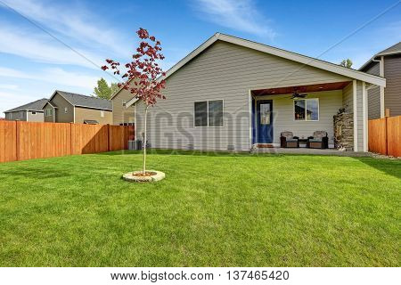 Nice Back Yard With Well Kept Lawn And View Of Covered Porch With Fireplace