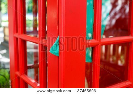 dress clamped door of red telephone box. she quickly hopped into a phone box, was in a hurry to call. dress clamped door red telephone booth. communication concept
