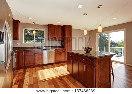 Spacious Kitchen Room With Bar, Brown Cabinets And Pendant Lights.