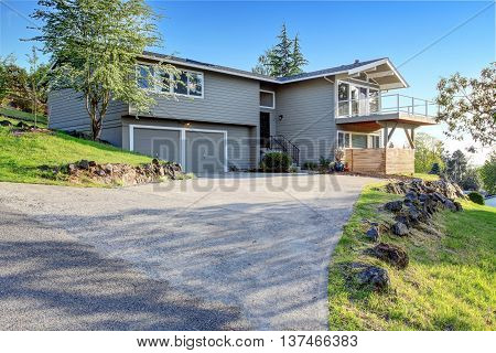 Two Story House Exterior With Gray Siding And Concrete Driveway.