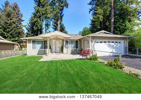 Curb Appeal Of Beige House With Well Kept Lawn And Garage