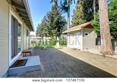 Backyard Deck With Tile Floor And Two Green Chairs. View Of Small Shed.