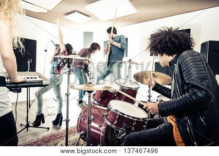 Rock band recording a track in a music studio