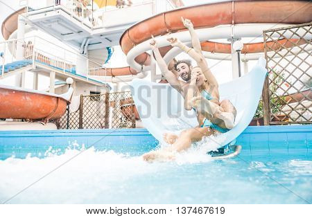 Friends having fun on a swimming pool slide - Couple splashing into water from a acquapark pipe