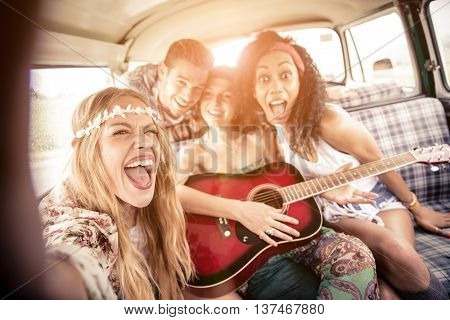 Group of friends traveling in a 70's van - Happy young people taking a selfie and having fun