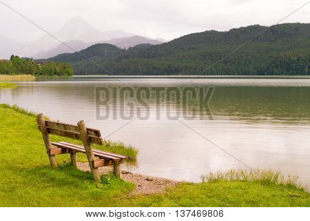 Bench by the lake  in the south of Bavaria, Germany and the mountains on horizon