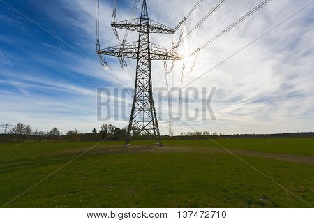 Electricity towers in landscape in sunset with cloudy skys