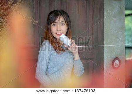 Cute girl talking through a tin phone.