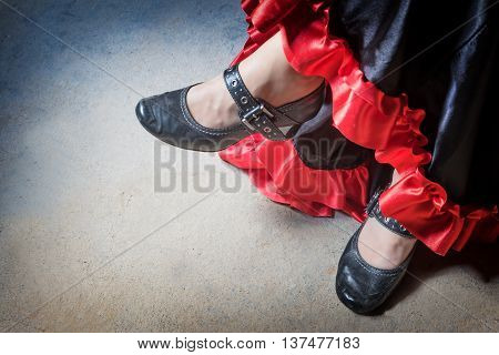 High angle view of legs of the Flamenco dancer. The photo has deliberately darkened edges. Horizontally.