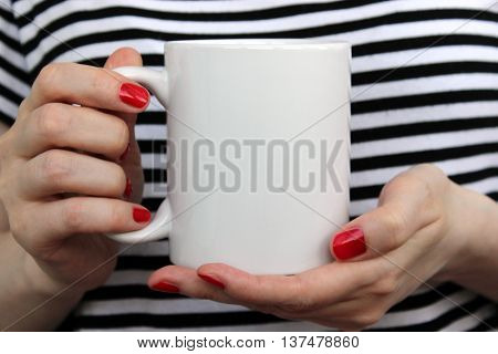 Girl is holding white cup mug in hands. Mockup for designs.