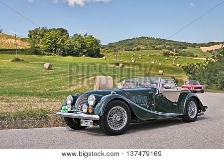 TREDOZIO FC ITALY: driver and co-driver on a vintage car Morgan 2.0 traveling in the hills during the rally